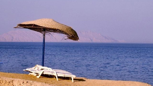 Chairs on beach with umbrella, vacation