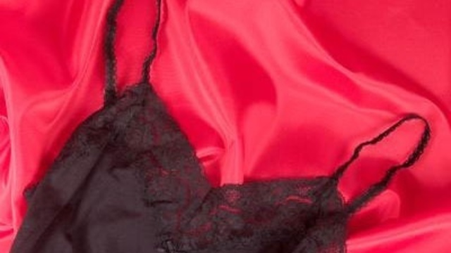 black lingerie on red silk sheets