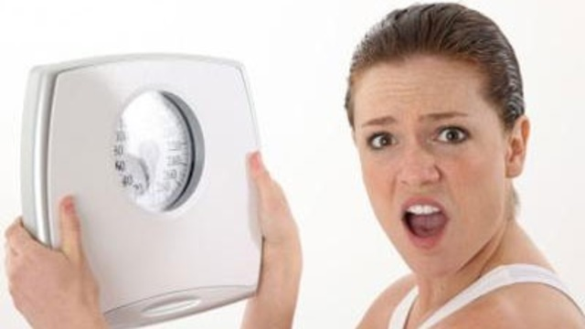 upset woman holding scale