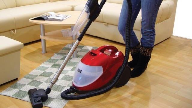 woman using vacuum cleaner on rug_8574150