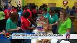 Volunteers stuff backpacks for children