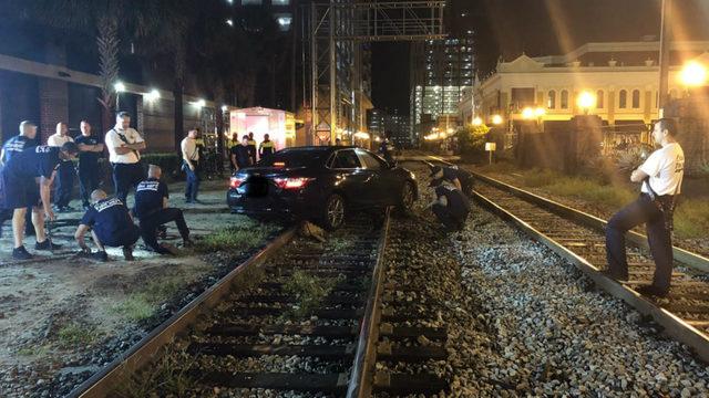 Car caught on train tracks, authorities say